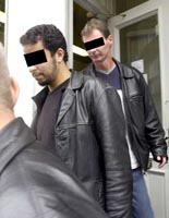 Unidentified suspects being led out of the bookstore in April 2002.